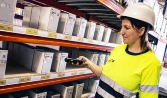 Mujer en almacén seleccionando productos de e-commerce mediante picking para servirlos